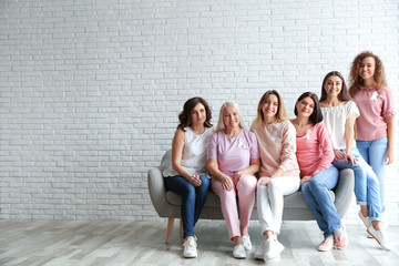 Group of women with silk ribbons on sofa against brick wall, space for text. Breast cancer awareness concept