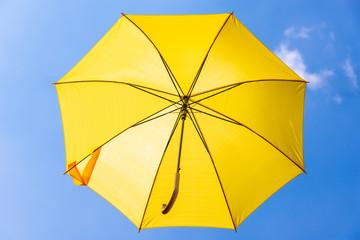 Gelber Regenschirm im blauen Himmel