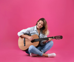 Young woman playing acoustic guitar on color background