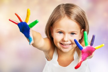 Little girl showing painted hands on  background
