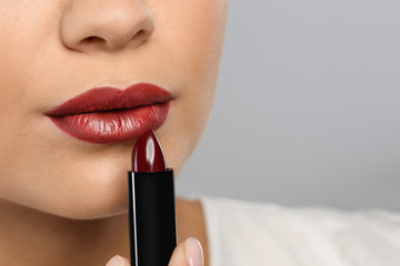 Beautiful woman applying dark lipstick on gray background, closeup. Space for text