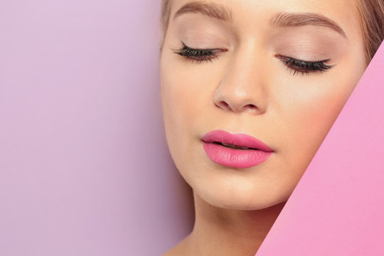 Young woman wearing beautiful lipstick on color background. Space for text