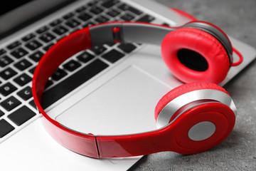 Modern headphones and laptop on table, closeup