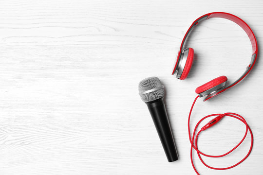 Headphones, microphone and space for text on white wooden background, top view