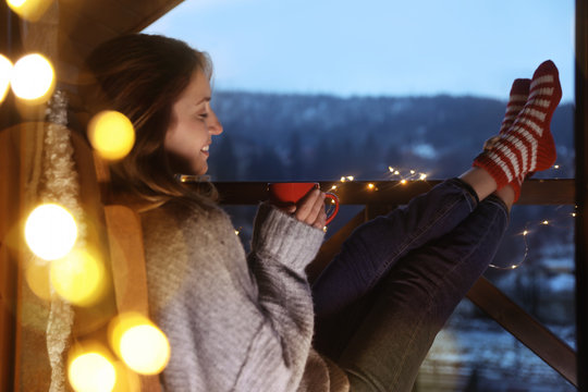 Woman with cup of hot beverage and Christmas lights resting on balcony. Winter evening
