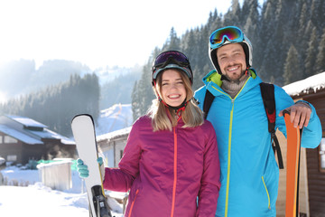 Happy couple with ski equipment spending winter vacation at mountain resort