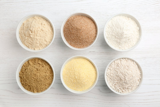Bowls with different types of flour on white wooden background, top view