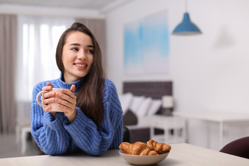 Young woman drinking coffee at table indoors, space for text. Winter season