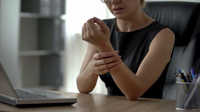 Female working on laptop, feeling wrist pain, osteoarthritis, joint inflammation