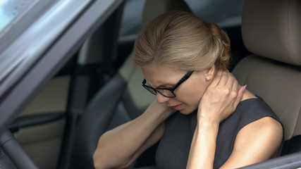 Exhausted woman feeling neck pain, sitting in automobile, spinal problem, health