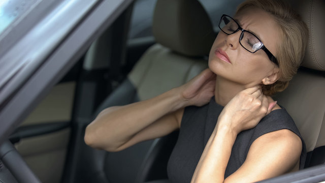 Tired business lady in car feeling strong neck pain, nerve inflammation, health