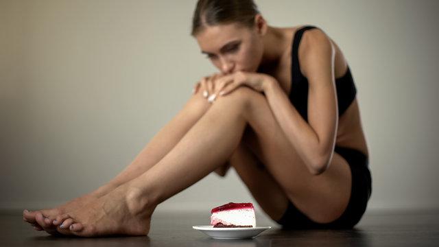 Slender girl looking at cake, hesitating to eat, disciplining mind and body