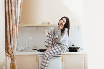 the young woman in a pajamas having breakfast and speaks by phone in kitchen