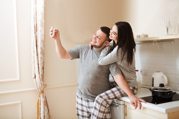 young couple the husband and the wife in pajamas take a selfie in kitchen of the house