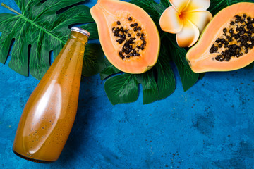 Summer tropical background with exotic juice papaya with chia seeds, green palm leaves on blue. Fruits background and summer drink. Top view, copy space