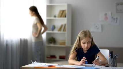 Lonely child drawing picture, strict mother standing by window, tense atmosphere