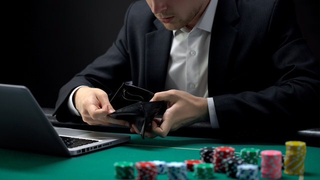 Nervous online gambler opening empty wallet, betting addiction, bankruptcy