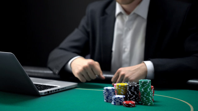 Online gambler with clenched fists waiting for bets results in front of laptop