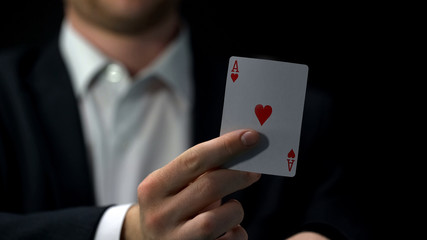 Male player holding ace card, business bluff strategy, chance to win, gambling