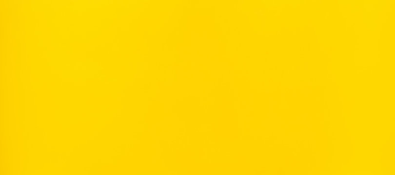 Vibrant yellow plastic surface background.