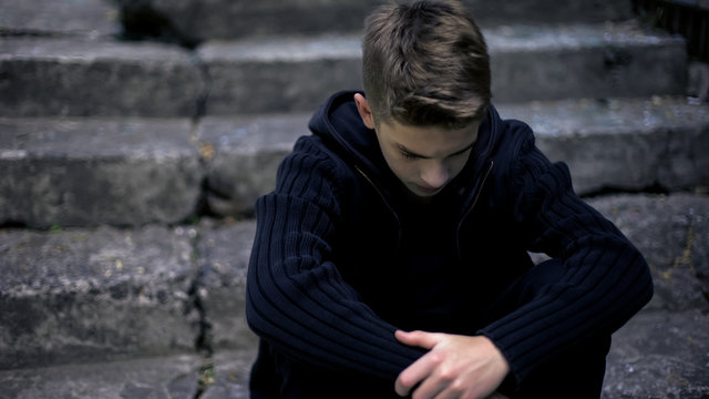 Sad teen sitting on old cracked steps, feeling grief and sorrow, parents loss