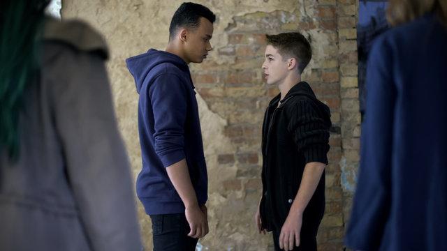 Boys conflicting, self-defense against school bullies, street violence, fight