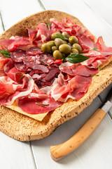 Spoed Fotobehang Voorgerecht Vassoio con salame, capocollo, prosciutto, olive e pane carasau