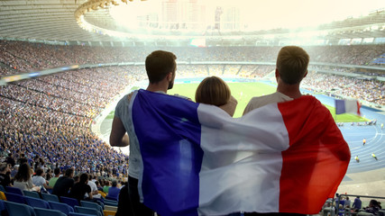 Football fans with French flag jumping at stadium, cheering for national team
