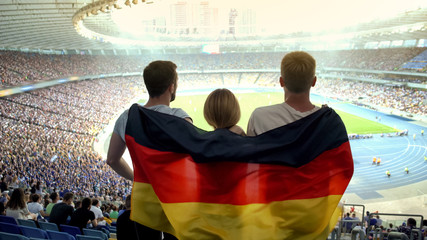 Football fans with German flag jumping at stadium, cheering for national team