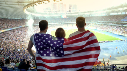 Football fans with American flag jumping at stadium, cheering for national team