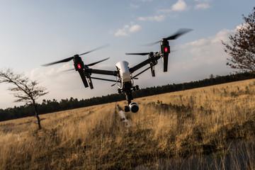 Surveillance drone flying over grassy landscape