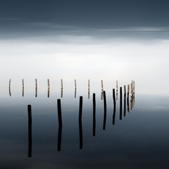 Scenic view of wooden post in lake against sky