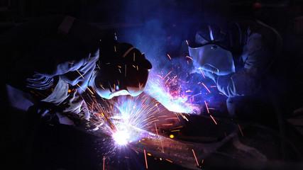 Welders welding metalwork in a factory
