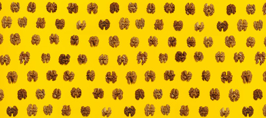 Walnuts halves in lines with hard shadow on yellow background, flat lay image.