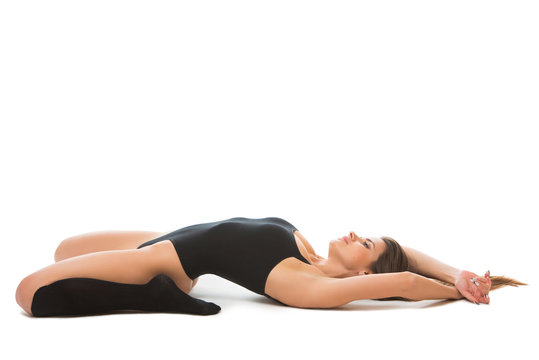 healthy fitness woman stretching, lying in a yoga pose on the floor .Young female wearing a sportswear: sports body and gaiters