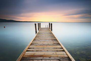 View of wooden pier in lake during sunset