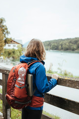 Female backpacker looking at lake while standing by railing against sky