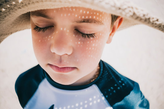 Close up of boy with eyes closed wearing hat on beach