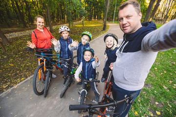 The theme family sports outdoor recreation. large family Caucasian 6 people mom dad and 4 children three brothers and sister ride bicycles in park on bicycle path. Father holds camera makes photo