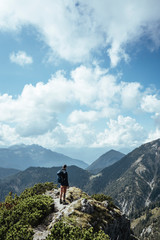 Rear view of male hiker with backpack looking at view while standing on mountain against cloudy sky during sunny day