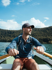 Man looking away while rowing boat on lake against blue sky during sunny day