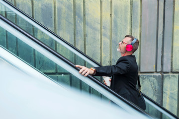 Side view of businessman listening music while standing on escalator against wall