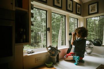 Boy using binoculars while looking through window on kitchen counter