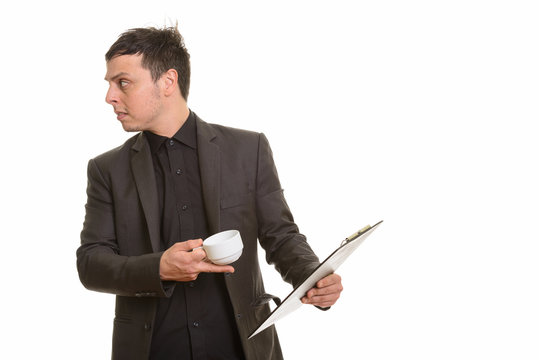 Studio shot of Caucasian businessman holding clipboard and coffe