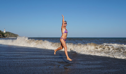 Beautiful woman runnig on the rolling waves on the beach