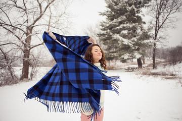 Playful teenge girl holding blanket in snow