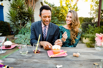 Smiling young multiethnic couple eating cupcake while sitting at table in backyard during cocktail party