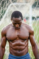 Shirtless muscular male athlete looking down while standing against net on soccer field