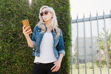 Woman blowing bubble while using smartphone against plants by fence at park