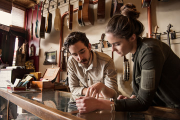 Couple standing behind counter in guitar shop